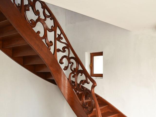 Gięte schody samonośne z rzeźbioną balustradą